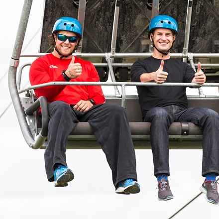 Three people smile and give a thumbs up as they ride the Skyride at Skyline Luge Calgary.