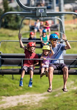 A dad and his two children ride the Skyride at Skyline Luge Calgary.