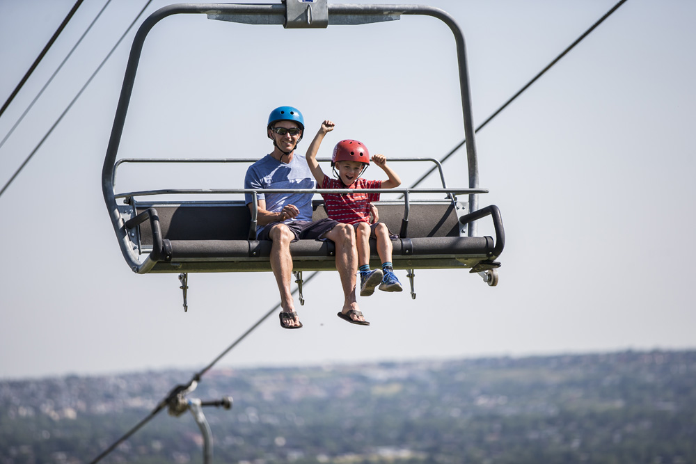 A dad and his son ride the Skyride at Skyline Luge Calgary.