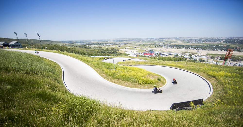 People riding their downhill karts round a large horseshoe corner at Skyline Luge Calgary.