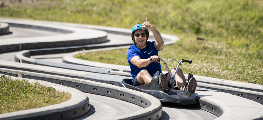 A man does a 'shaka' hand sign at the end of the track at Skyline Luge Calgary.