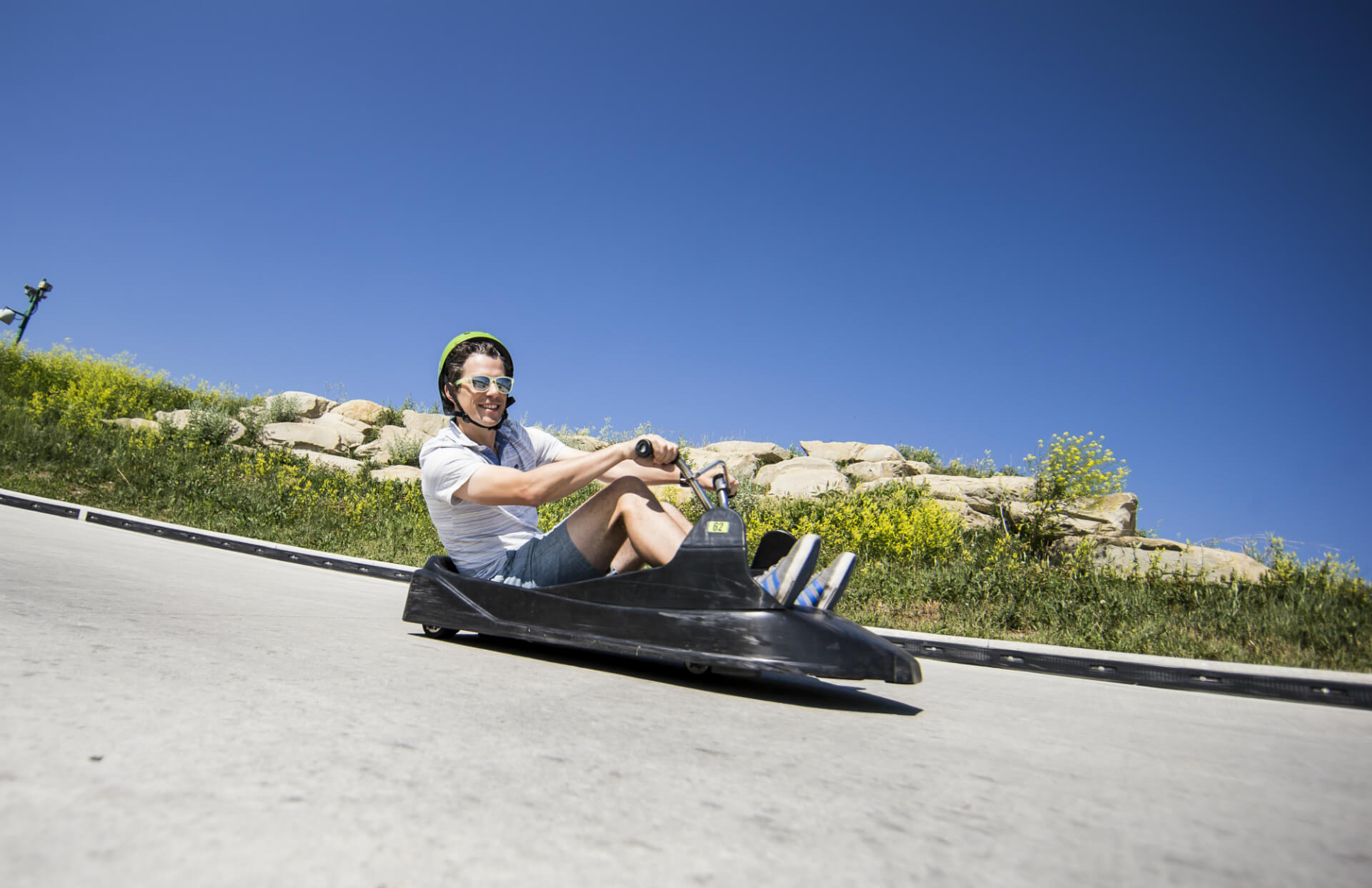 A man grinning as he corners his downhill kart at Skyline Luge Calgary.