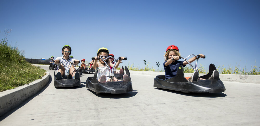 Two children lead the way down the track in their downhill kart at Skyline Luge Calgary.